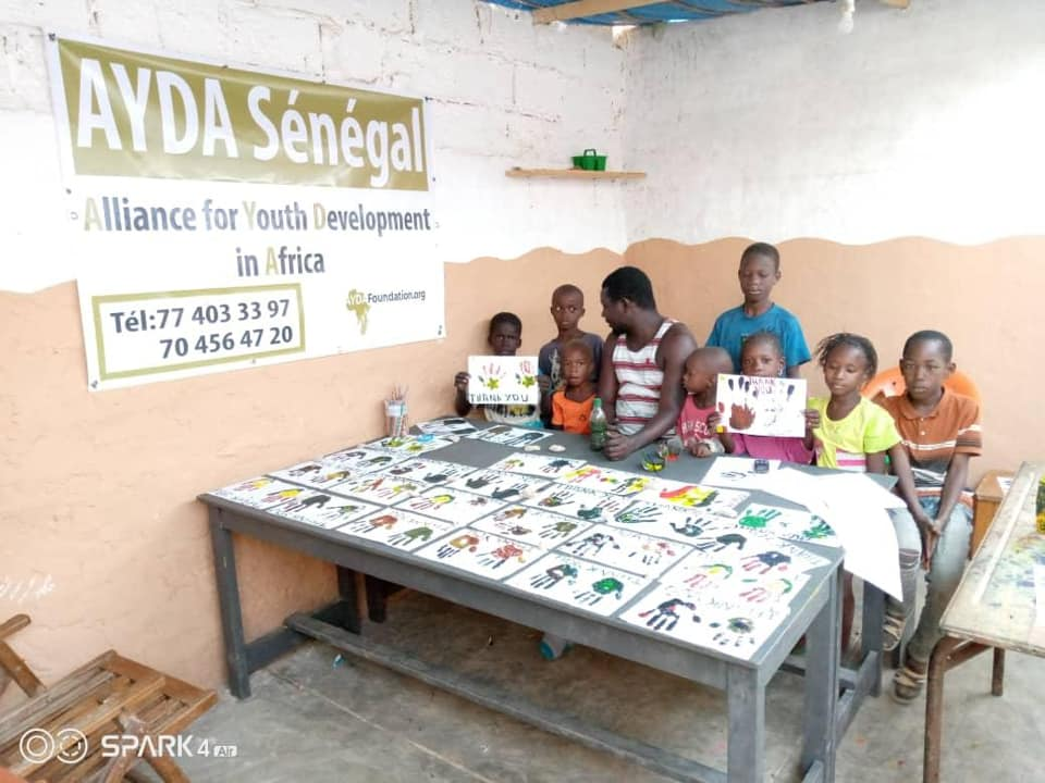 Kids in Senegal sitting with an instructor with a banner of AYDA Senegal